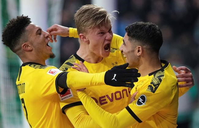 Dortmund's Erling Haaland, center, celebrates scoring a goal against Werder Bremen during the German Bundesliga soccer match in Bremen, Germany, Saturday Feb. 22, 2020. (Peter Steffen/DPA via AP)