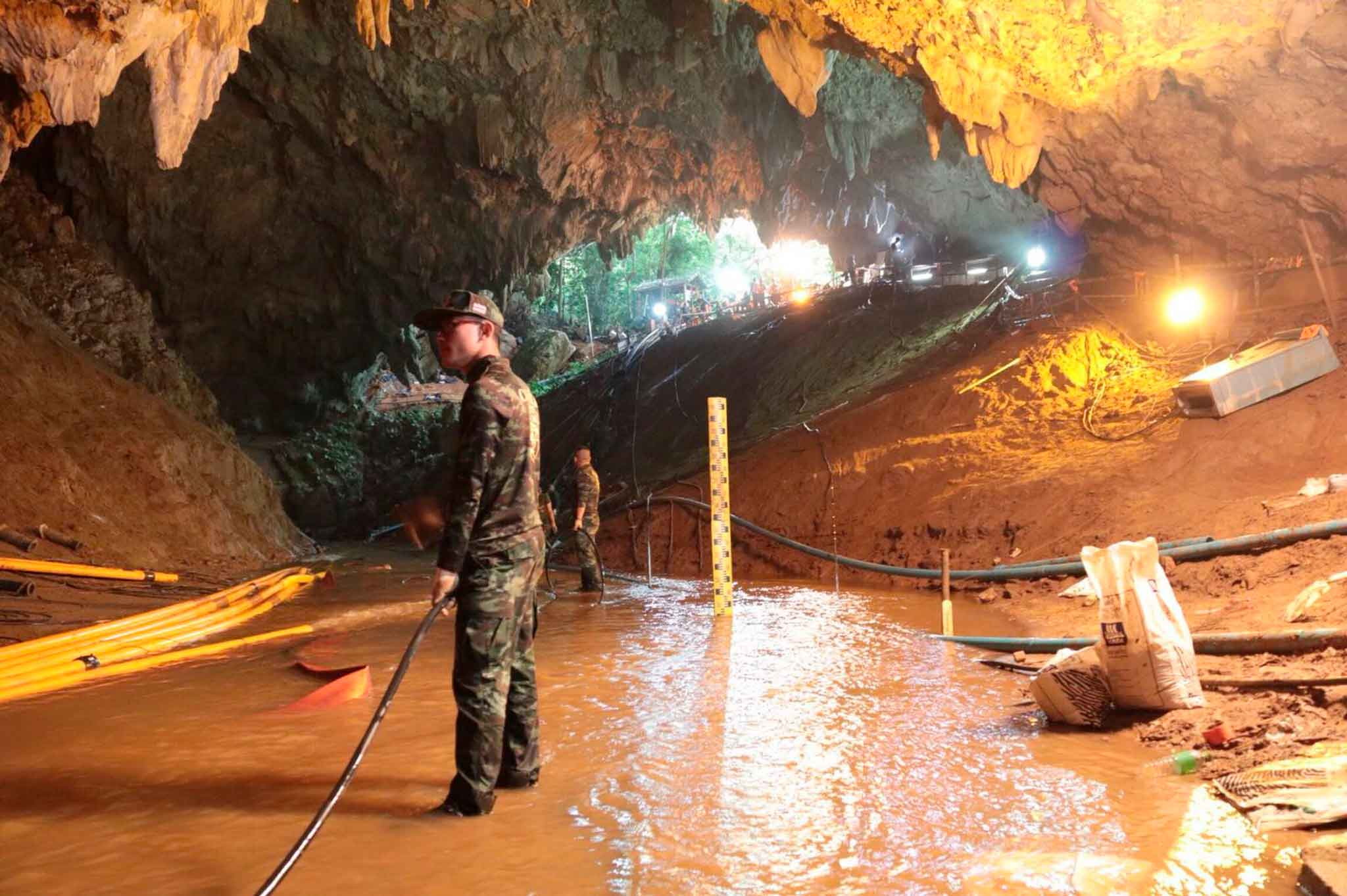 Thai rescue teams arrange water pumping system at the entrance to a flooded cave complex. (Royal Thai Navy via AP)