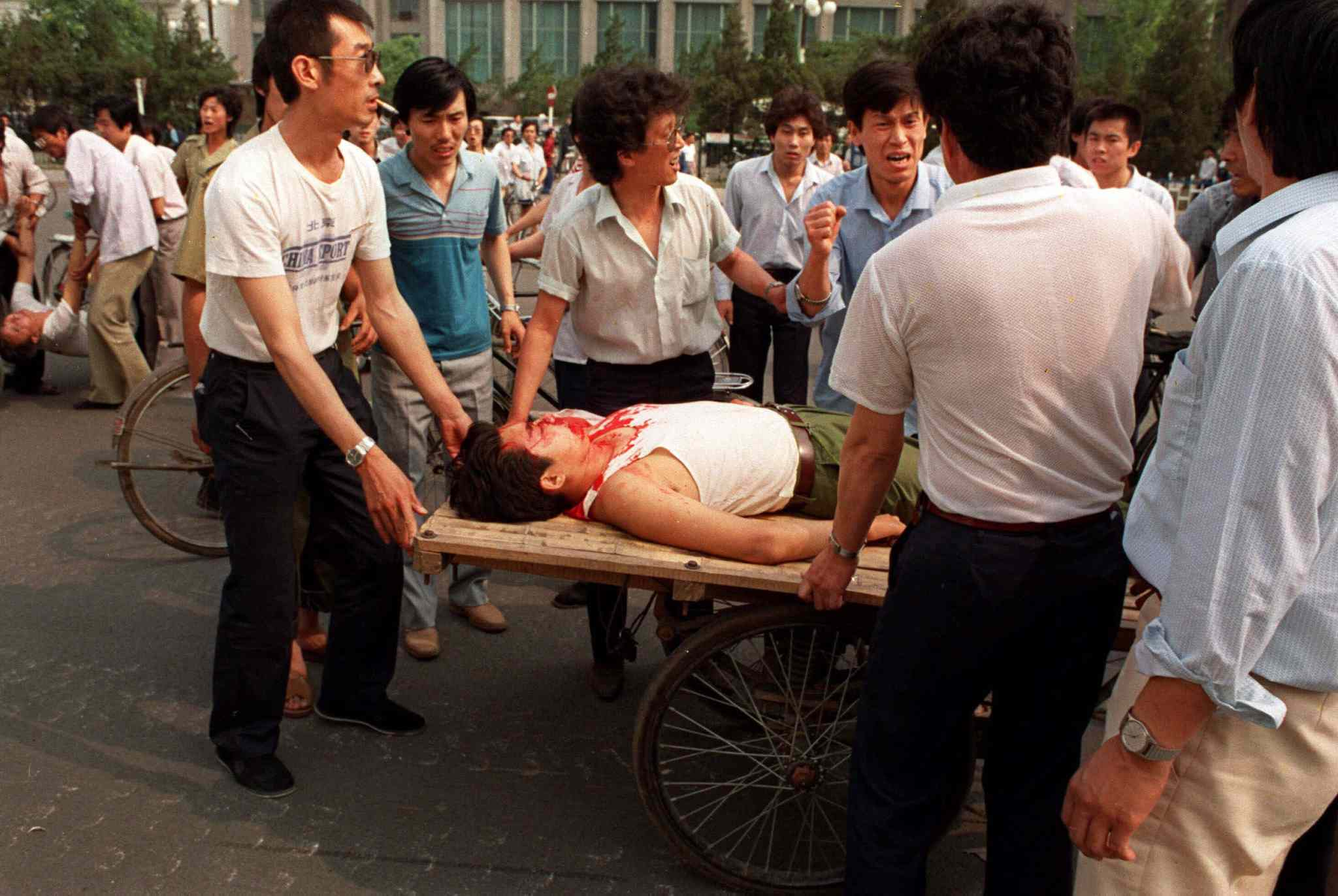 Beijing residents load a wounded person on a rickshaw flatbed shortly after Chinese soldiers opened fire on a crowd in Tienanmen Square in this June 4, 1989 photo.