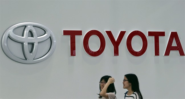 FILE - In this May 8, 2014 file photo, visitors walk under the logo of Toyota Motor Corp. at its gallery in Tokyo. Toyota remains No. 1 in global vehicles sales after the first six months of this year, followed by Volkswagen which bumped General Motors out of second place as the U.S. automaker grapples with a recall scandal. Japan's Toyota Motor Corp. announced Wednesday, July 30, 2014 that January-June global sales totaled 5.097 million vehicles, up nearly 4 percent from a year earlier. (AP Photo/Koji Sasahara, File)