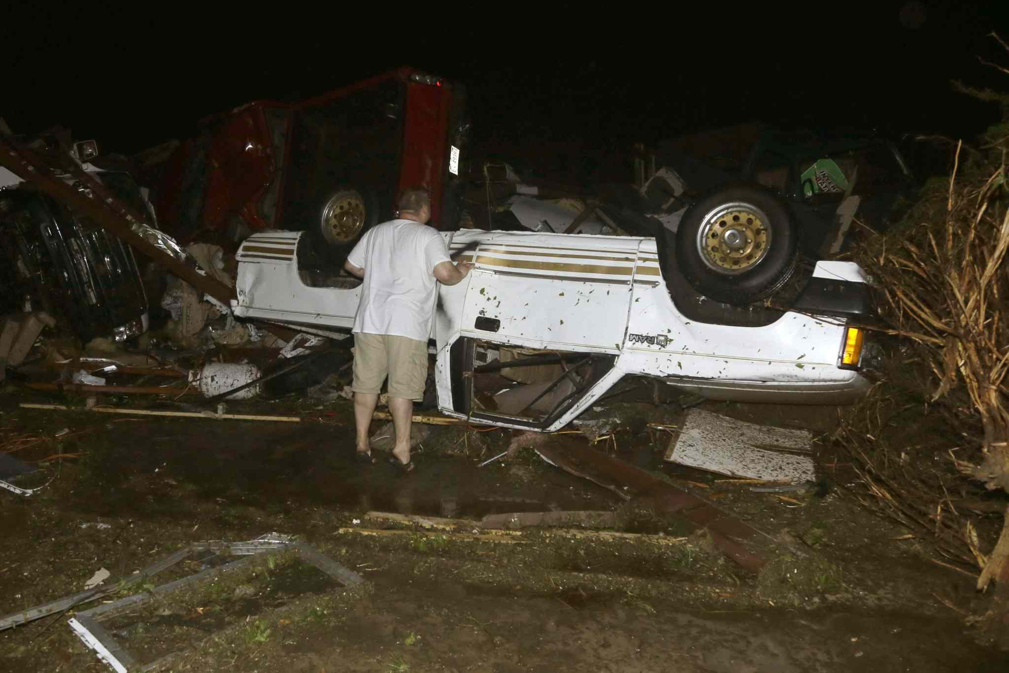 John Ward, an automobile and RV dealer, looks at damage to one of his trucks in Mayflower, Ark., Sunday, after a tornado struck.
