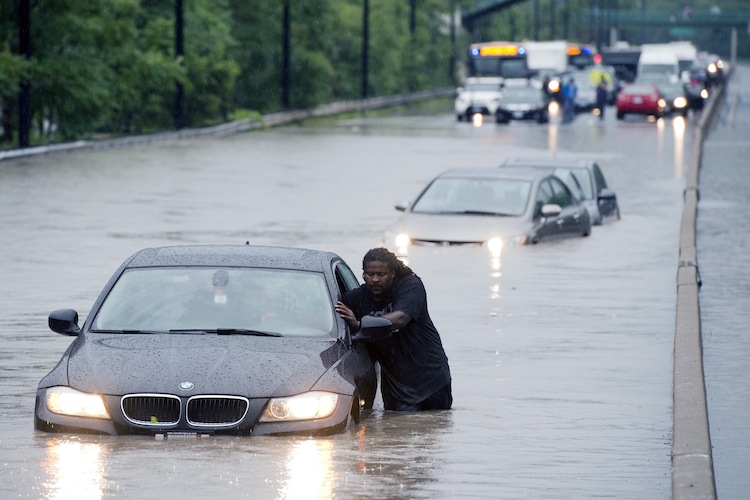 A tow truck driver floats a car out of the Don Valley Parkway. (Frank Gunn / The Canadian Press)