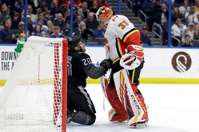 Calgary Flames goaltender David Rittich (33) knocks down Tampa Bay Lightning center Blake Coleman (20) after the two collided during the second period of an NHL hockey game Saturday, Feb. 29, 2020, in Tampa, Fla. (AP Photo/Chris O'Meara)