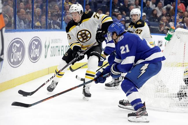 Boston Bruins defenseman Charlie McAvoy (73) looks to move the puck past Tampa Bay Lightning center Brayden Point (21) during the second period of an NHL hockey game Thursday, Dec. 12, 2019, in Tampa, Fla. (AP Photo/Chris O'Meara)