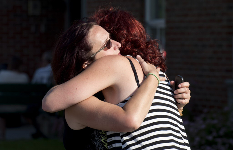 Federique Mailloux hugs a friend as they wait outside an emergency centre for news. (Paul Chiasson / The Canadian Press)