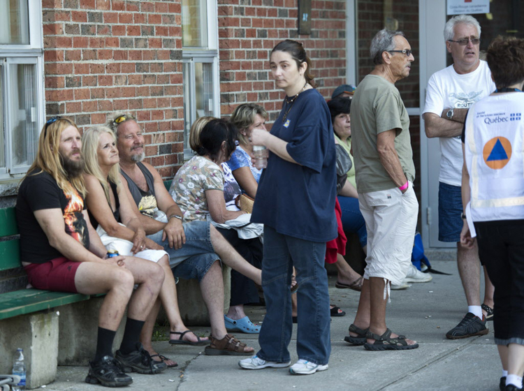 Residents wait outside an emergency centre for news of family and friends. (Paul Chiasson / The Canadian Press)