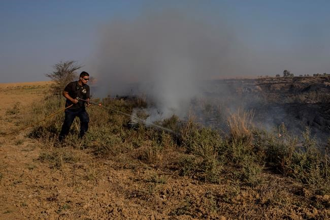 Israeli worker with the Nature and Parks Authority extinguishes a fire started by a kite with attached burning cloth launched by Palestinians from Gaza Strip, near the Israel Gaza border, Thursday, Aug. 9, 2018. (AP Photo/Tsafrir Abayov)
