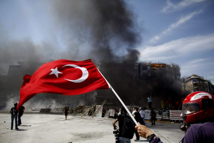 A protester raises a Turkish flag as a fire burns a barricade during clashes in Taksim square in Istanbul Tuesday.