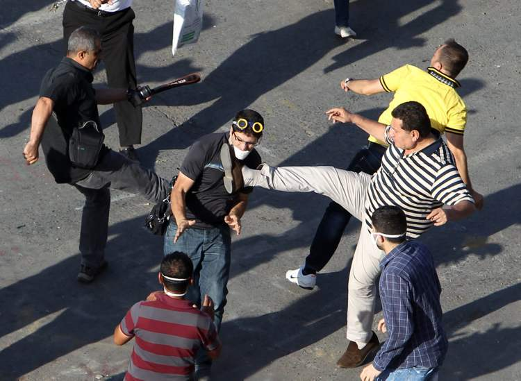 A man who had thrown a stone at a protester (centre) runs to avoid being attacked, during clashes in Taksim Square in Istanbul Tuesday. (CP)