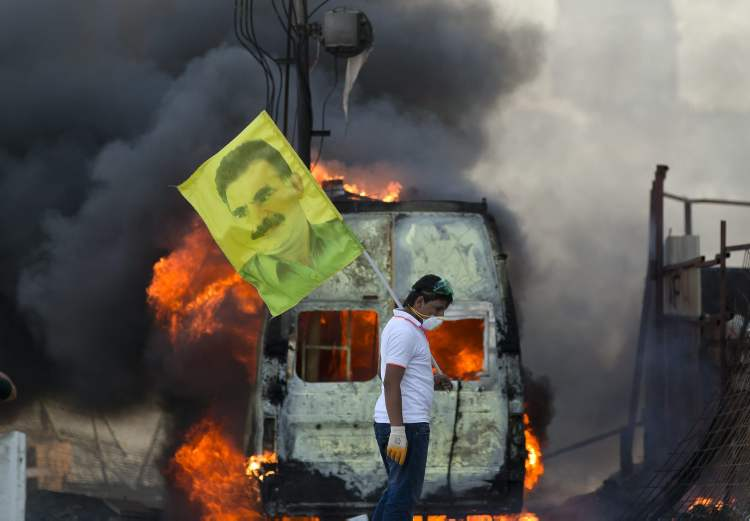 A protester holds a flag depicting jailed Kurdish rebel leader Abdullah Ocalan as a van burns during clashes at the Taksim Square in Istanbul Tuesday.
