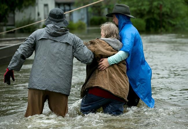 Volunteers help a woman after she was rescued by boat from her home in Beaumont, Texas, in the aftermath of Harvey on Wednesday Aug. 30, 2017. (Jay Janner/Austin American-Statesman via AP)