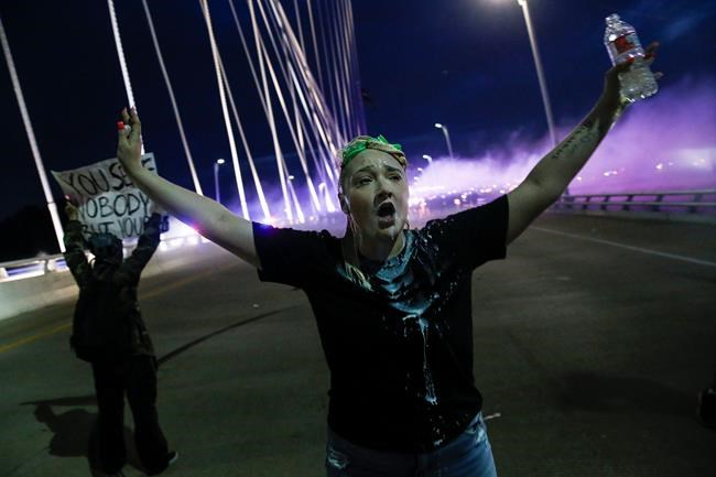 In this Monday, June 1, 2020, photo, a protester raises her arms on the Margaret Hunt Hill Bridge while demonstrating against police brutality in Dallas. Protests continue over the death of George Floyd, a black man who died after being restrained by Minneapolis police officers on May 25. (Ryan Michalesko/The Dallas Morning News via AP)