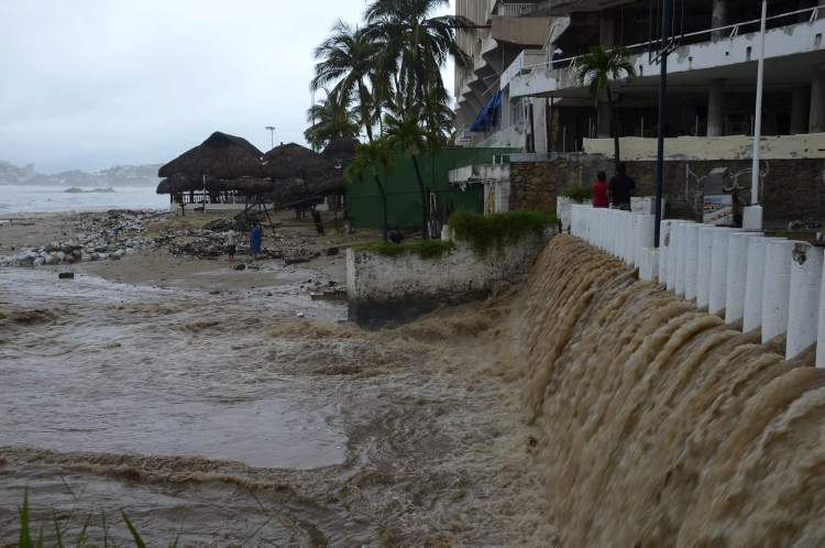 Rain water pours into the beach due to heavy rains caused by Tropical Storm Manuel in the Pacific resort city of Acapulco, Mexico, Sunday, Sept. 15, 2013 (AP Photo/Bernandino Hernandez)