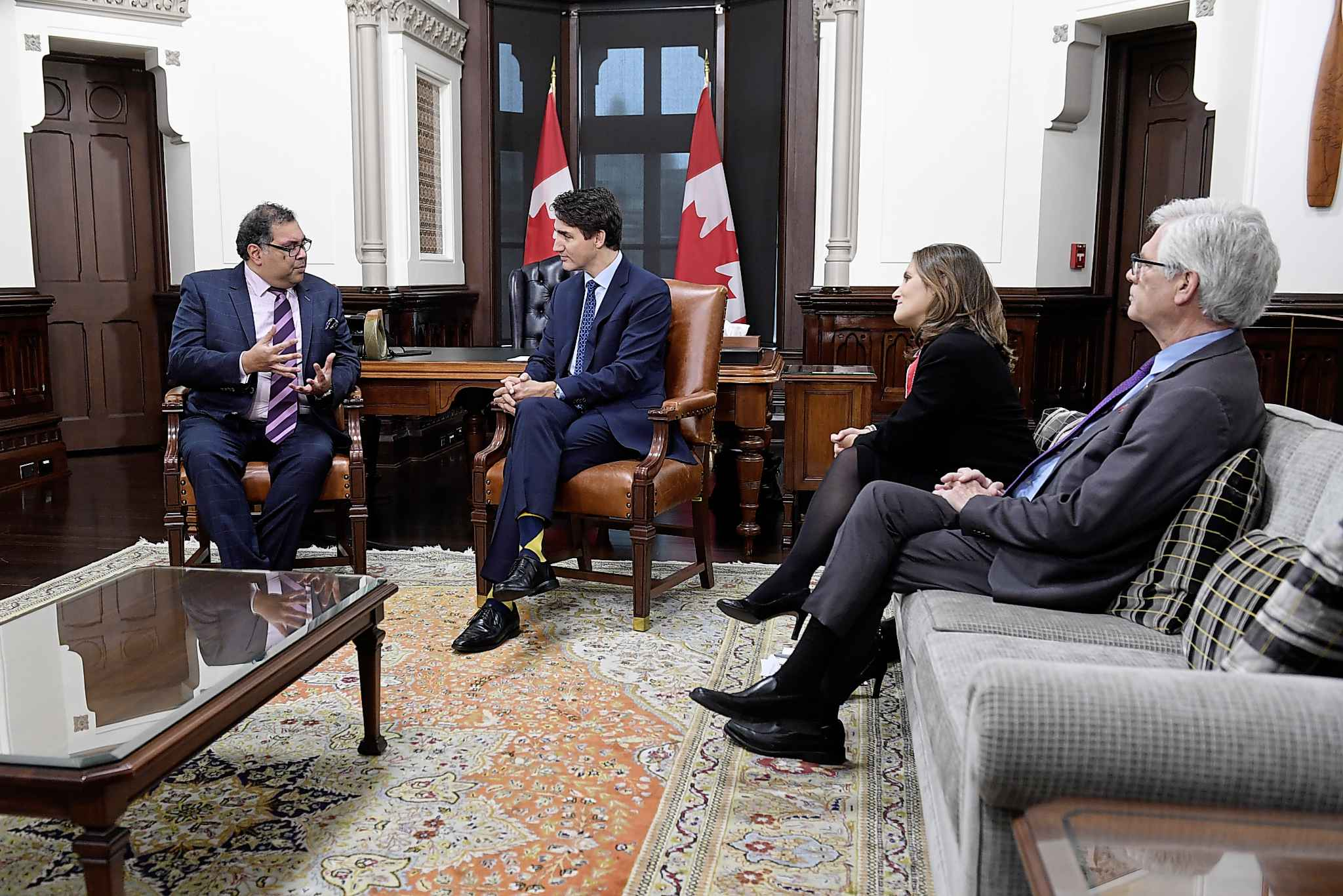 Deputy Prime Minister Chrystia Freeland and Jim Carr, right, look on as Prime Minister Justin Trudeau speaks with Calgary mayor Naheed Nenshi in his office on Parliament Hill. (Adrian Wyld / Canadian Press)