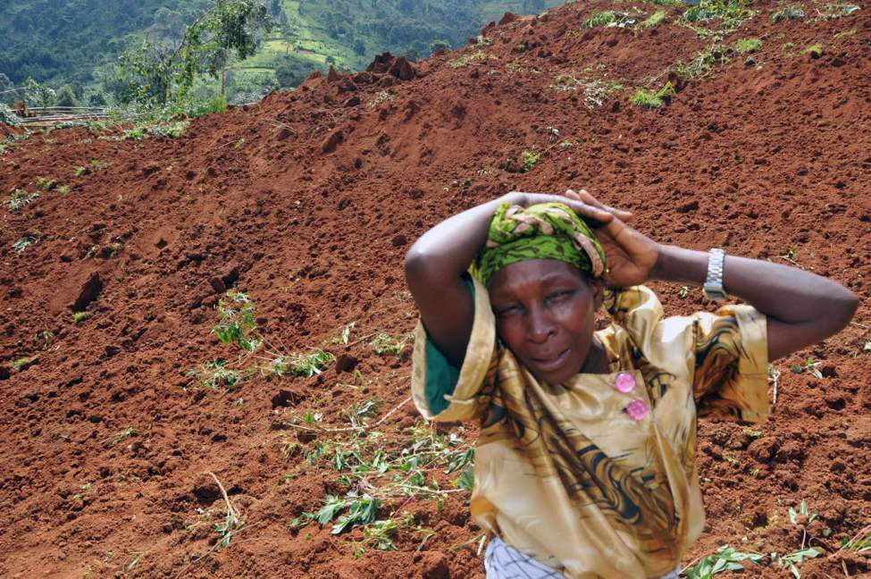 A woman cries for her four children she lost in a landslide in Bududa,  east of Uganda capital Kampala. Massive landslides induced by torrential rains destroyed three villages in the mountainous district of Bududa in eastern Uganda Monday, killing scores of people officials said. (AP Photo / Stephen Wandera)