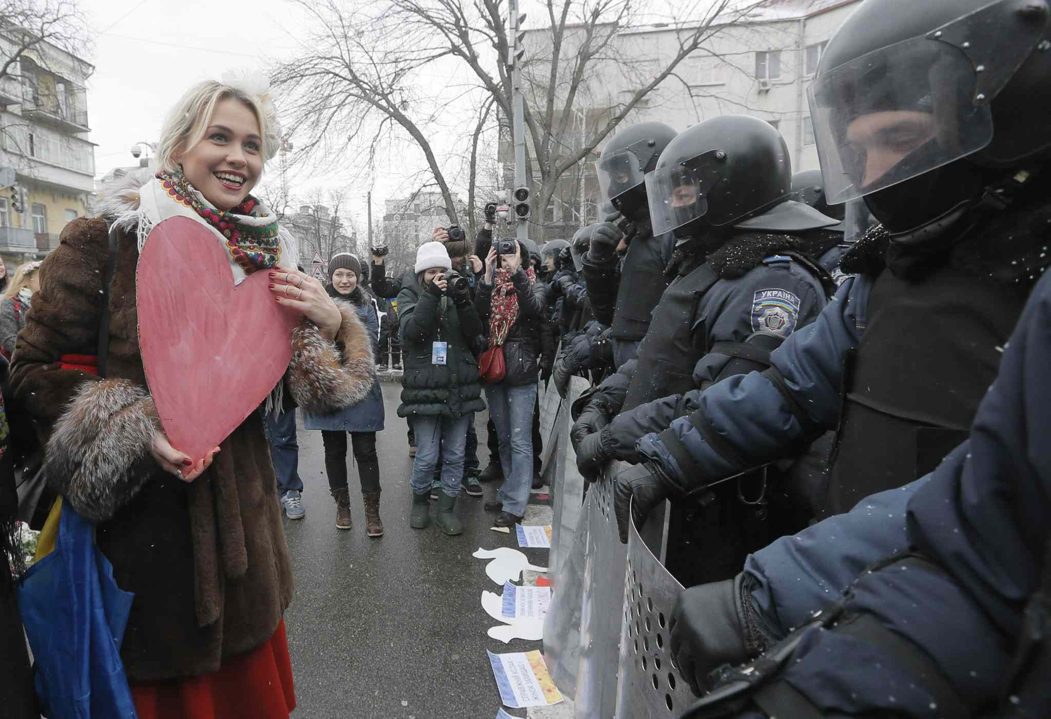 A pro-European union activist holds a cut-out of paper heart as she addresses to police at the presidential office in Kiyv, Ukraine, Sunday.