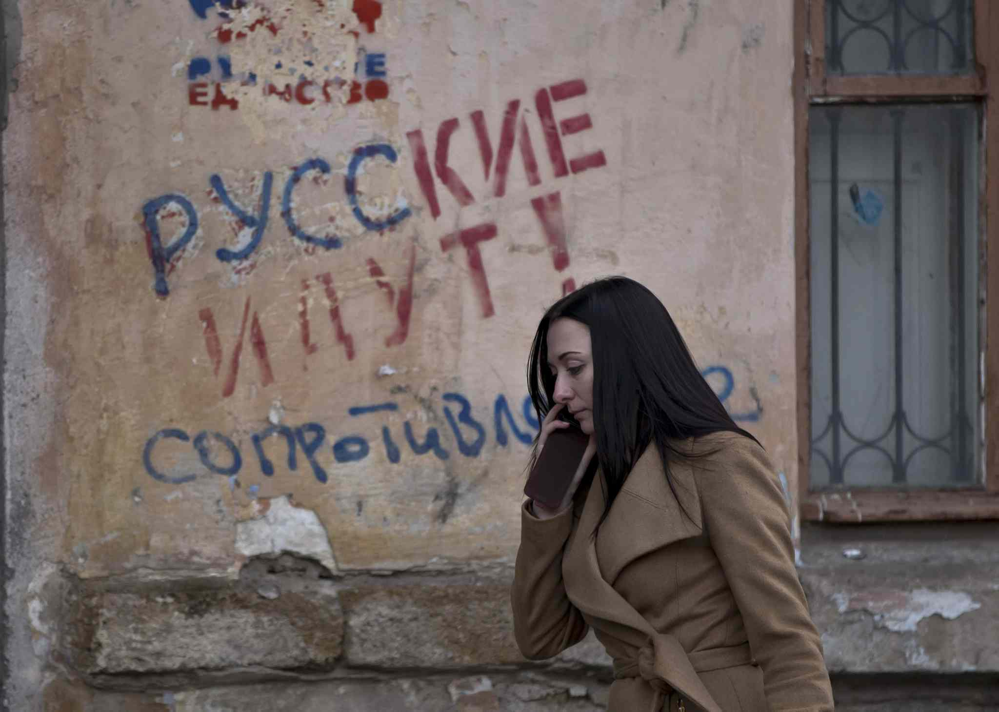 "A woman passes by a graffiti that reads ""The Russians are coming - Resistance"" in Simferopol, Ukraine, Friday. Ukraine lurched toward breakup Thursday as lawmakers in Crimea unanimously declared they wanted to join Russia and would put the decision to voters in 10 days."