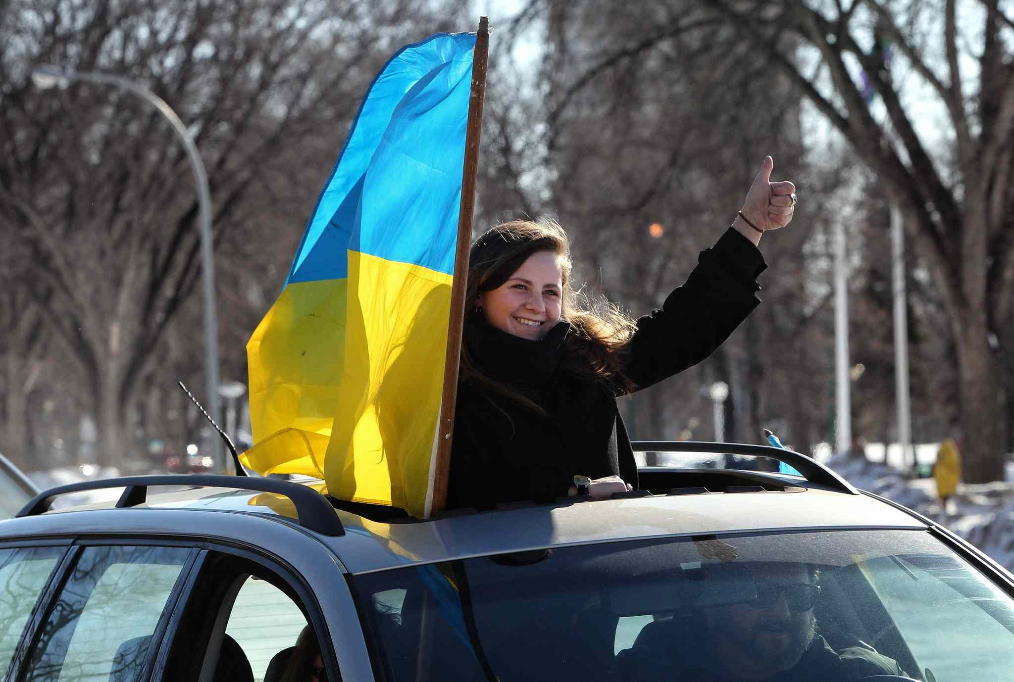 Daria Lytwyn gives the thumbs-up from the sun roof of a car during a car rally held by the Ukrainian Canadian Congress — Manitoba Provincial Council to raise awareness about the situation in Ukraine and showing solidarity with the Ukrainian people.