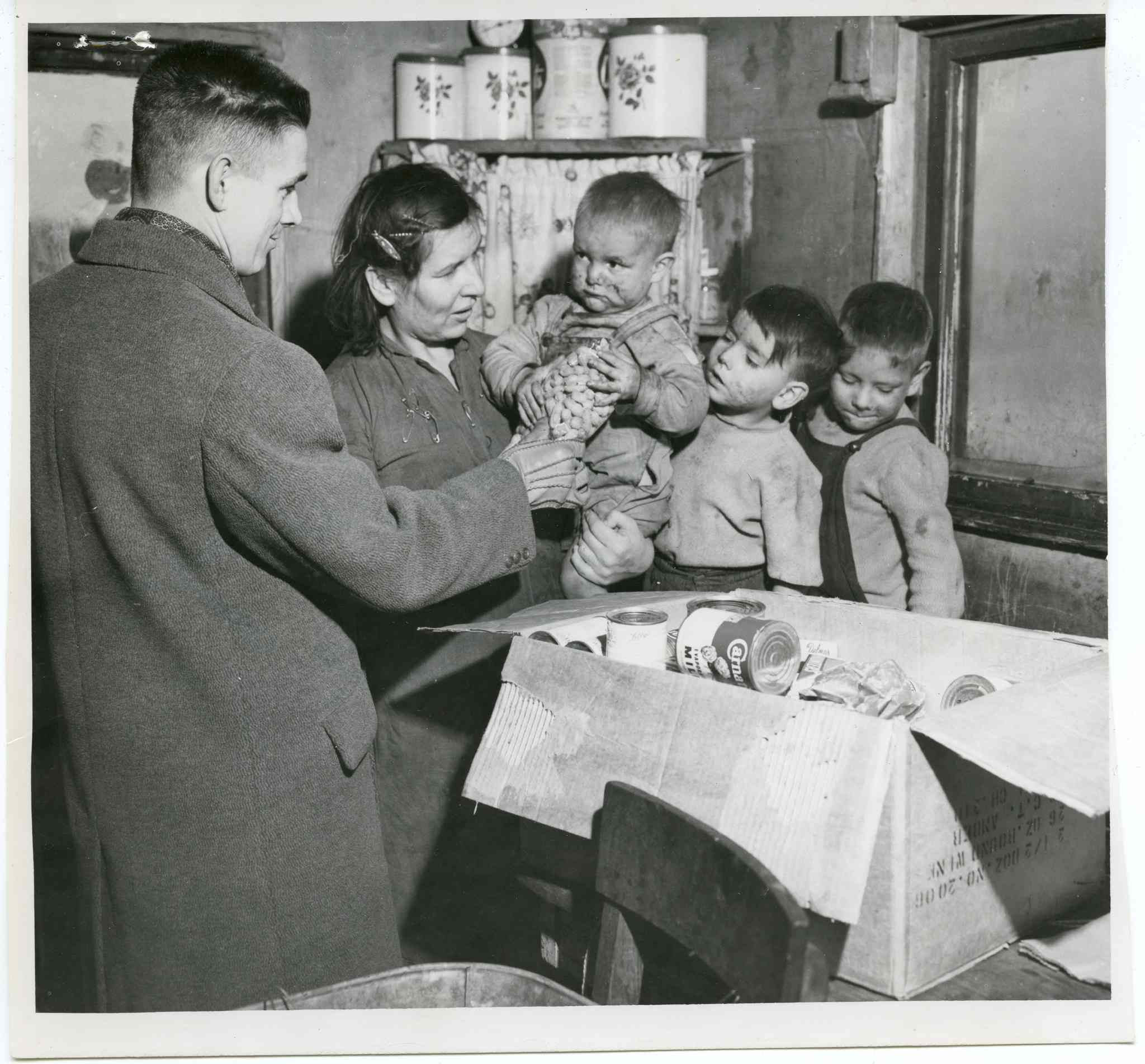 December 24, 1951:  After seeing a Tribune story describing the squalor of the Metis shack settlement in the southwest part of the city, an MTS group used $10 of an office fund to buy groceries for a needy family of the area. Shown presenting the groceries to Mrs. Archie Cardinal and three of her eight children is Joe Peters, head of the plants records department.
