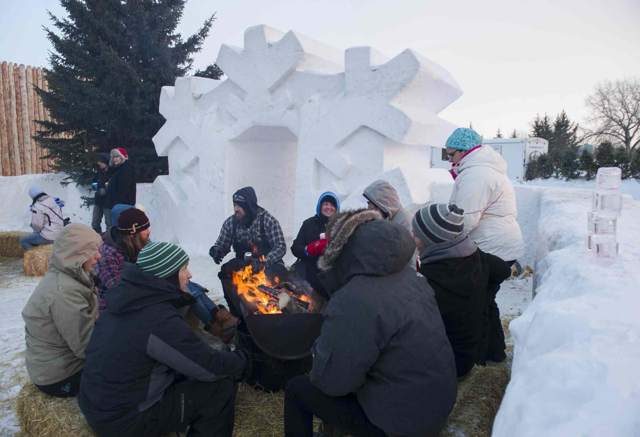 Festival-goers warm up by the fire at Festival du Voyageur on Saturday, Feb. 22.