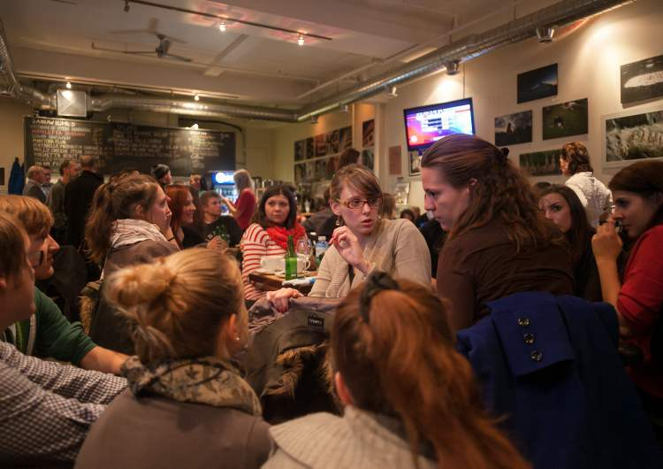 Anne Lacroix (centre) talks with Emmanuelle Renault (centre right) and others at the Winnipeg Free Press News Café on Tuesday night, where people crammed in to watch the 2012 U.S. election results.  (Melissa Tait / Winnipeg Free Press)