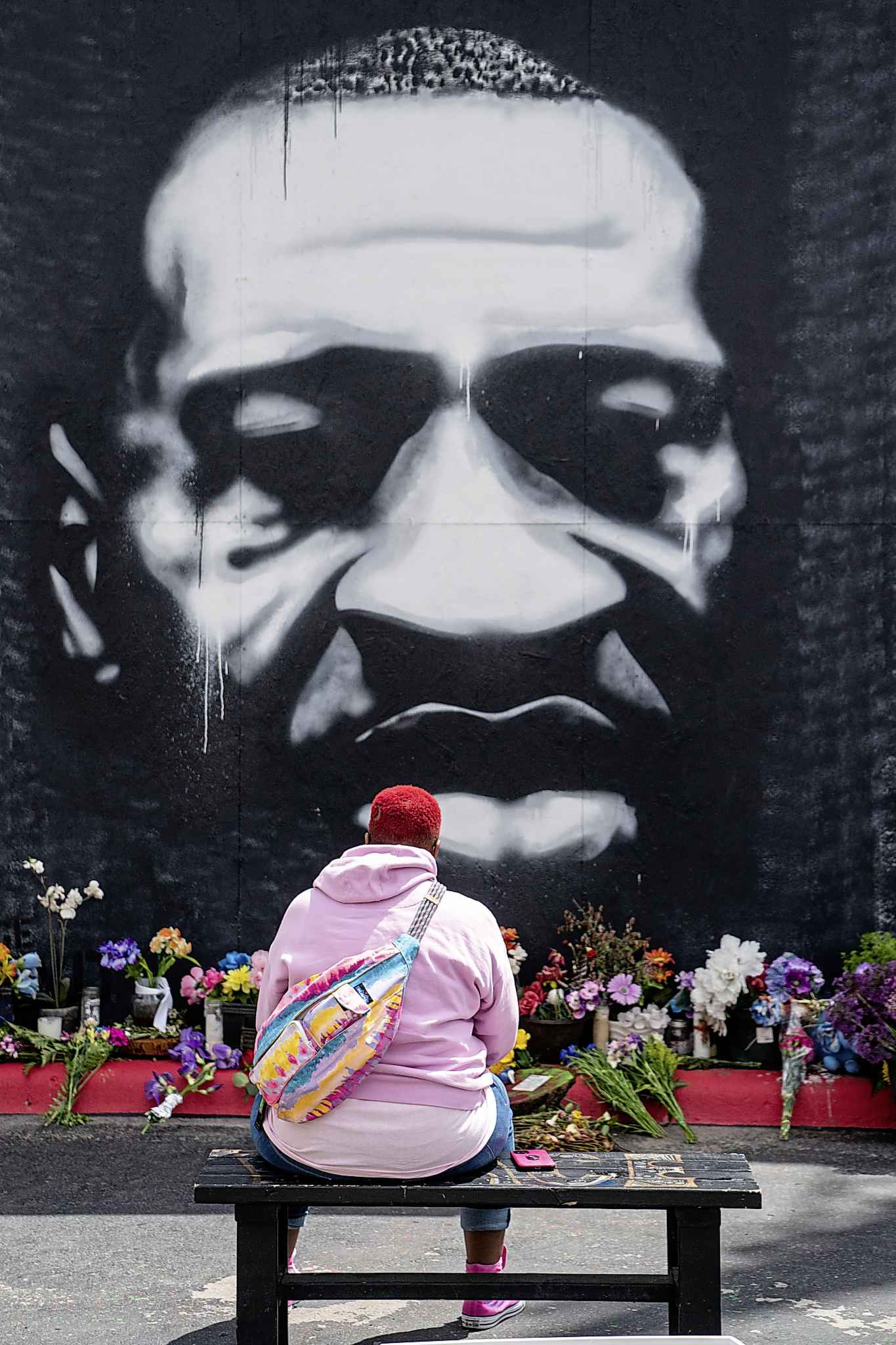 Myisha T. Hall, of Las Vegas, sits on a bench in front of a large mural depicting the late George Floyd, as people from across Minneapolis, and the world gather to visit the George Floyd Memorial Square on Tuesday, May 25, 2021, in Minneapolis, MN. (Kent Nishimura/Los Angeles Times/TNS)