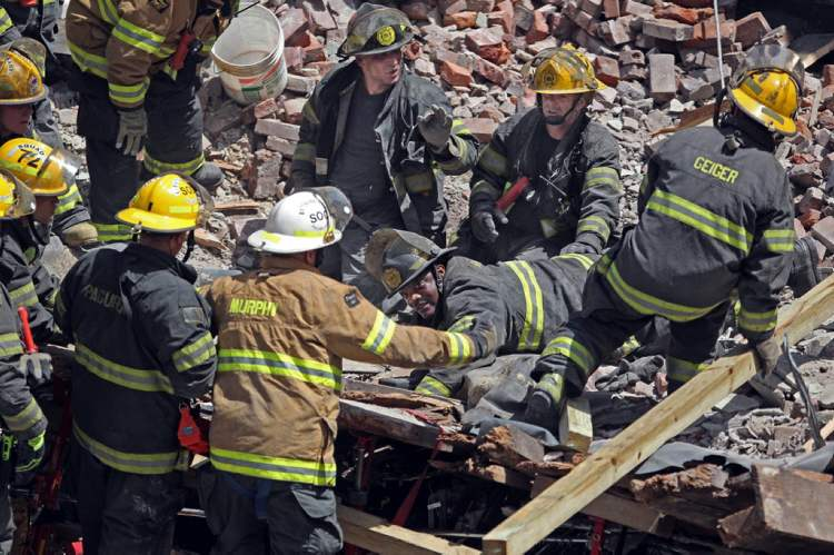 A Philadelphia firefighter (center) lays in the rubble with his hand thrust into the empty area as emergency personnel go through the rubble looking for survivors.