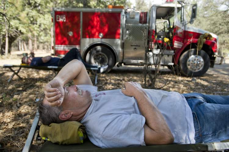 Sacramento River Fire District Captain Jerry Winters, 61, rests at base camp before the start of the night shift with Engineer Scott Stanfield fighting the Rim fire in the Stanislaus National Forest.