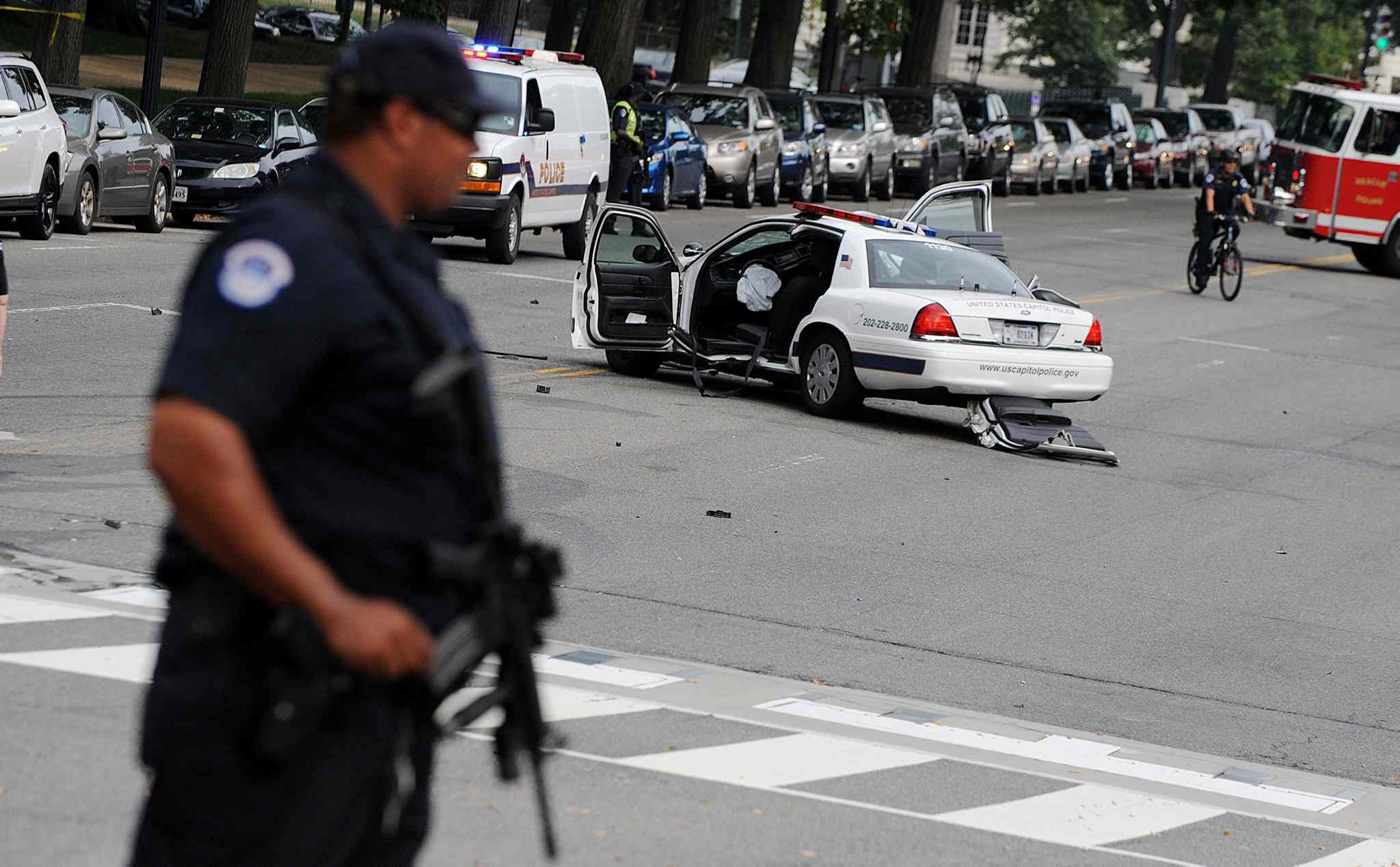 A U.S. Capitol police car sits wrecked in the street as an officer surveys the scene.