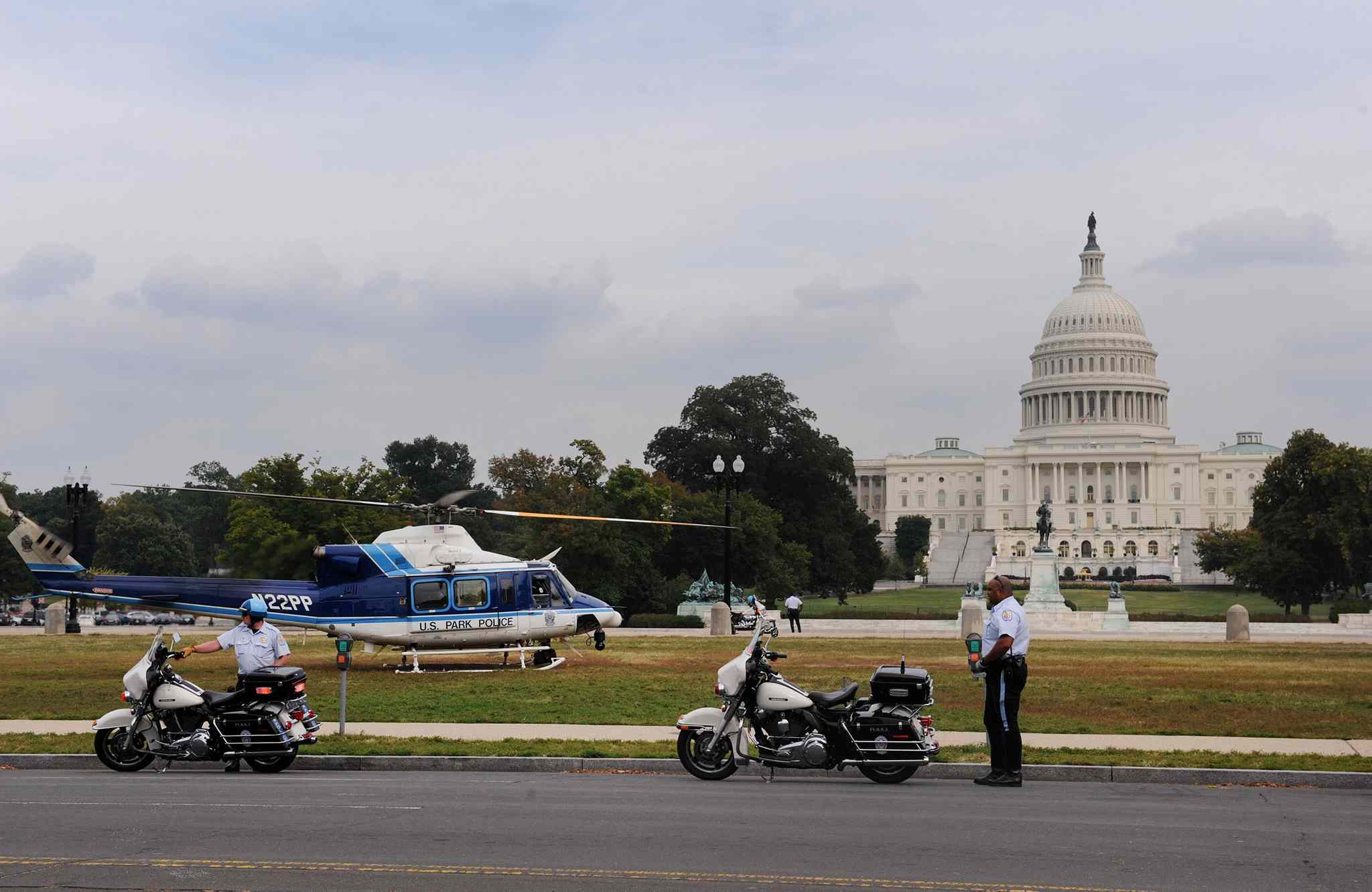 A police helicopter sits on the grass near the U.S. Capitol.