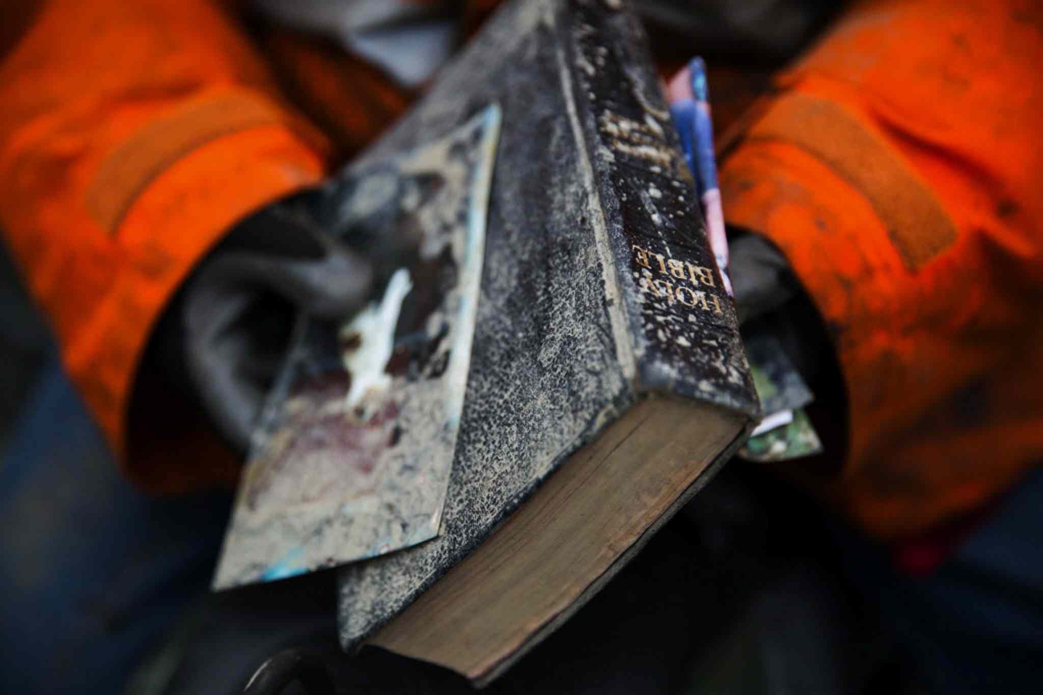 Elaine Young holds a bible pulled out of the debris field from the mudslide above the North Fork of the Stillaguamish River onto Highway 530, as recovery efforts are underway, near Oso, Wash.