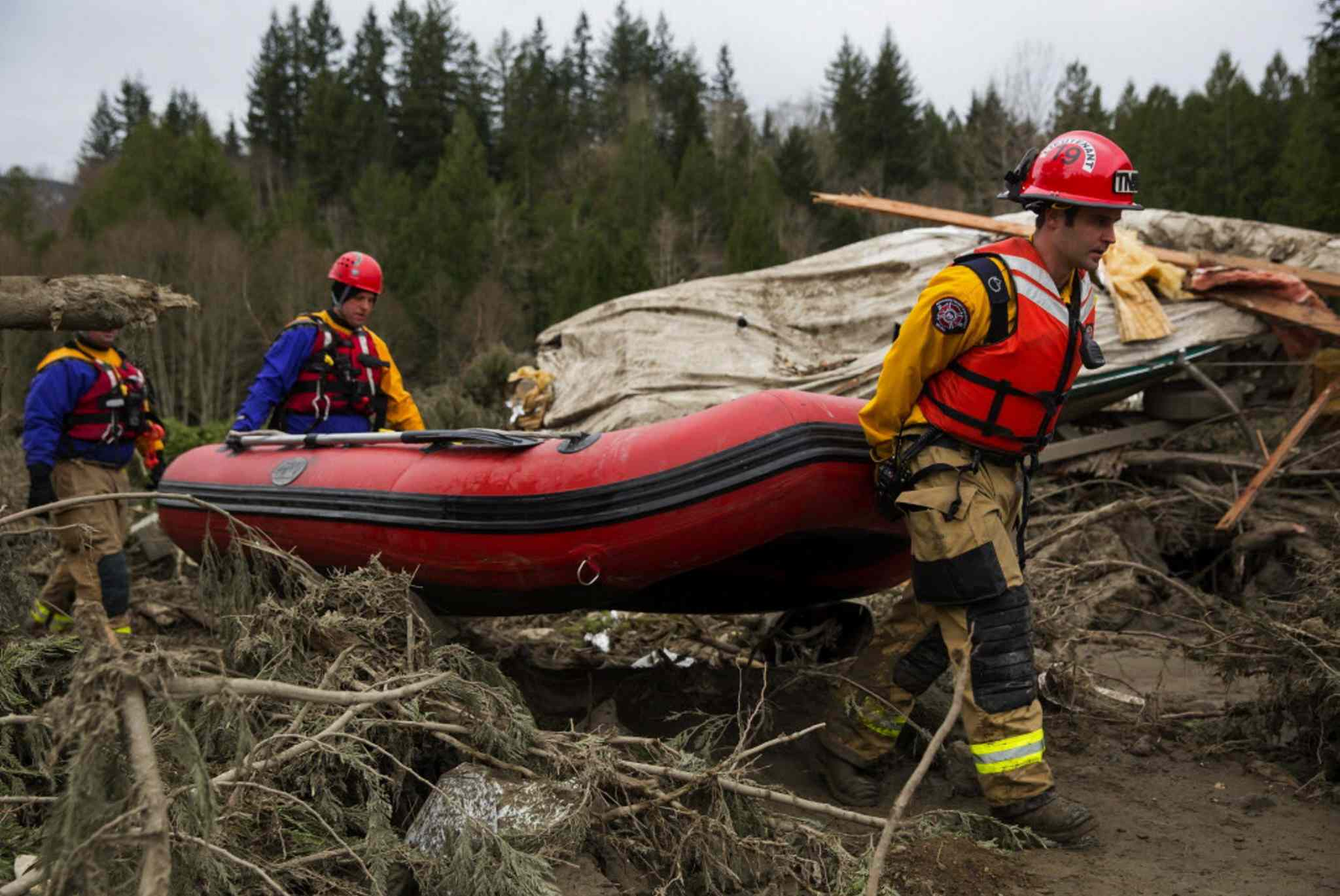 Rescue workers carry an inflatable boat to the flooded area in the debris field caused by the massive mudslide above the North Fork of the Stillaguamish River onto Highway 530, as recovery efforts are underway.
