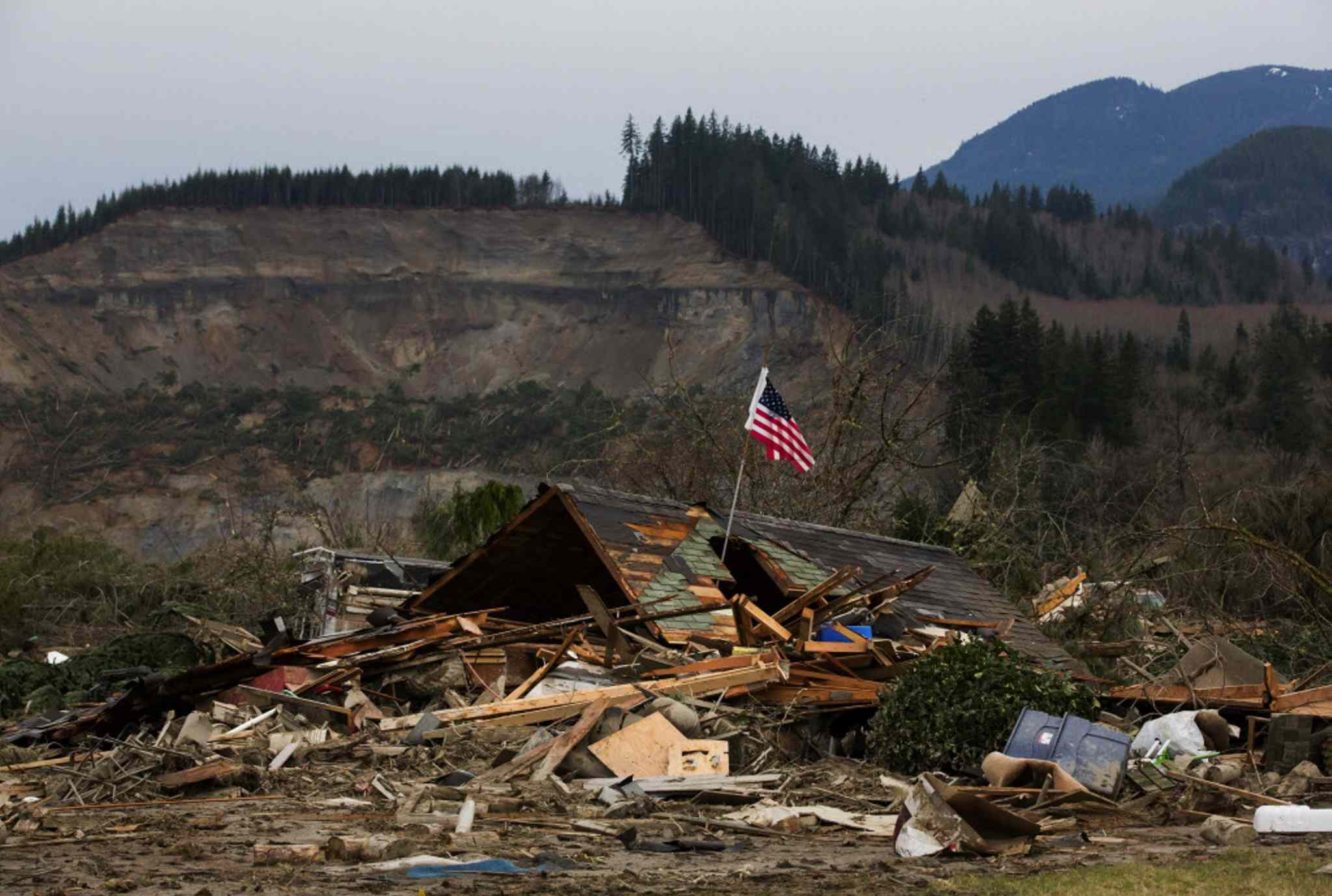 A damaged home sits in the debris field caused by the massive mudslide.