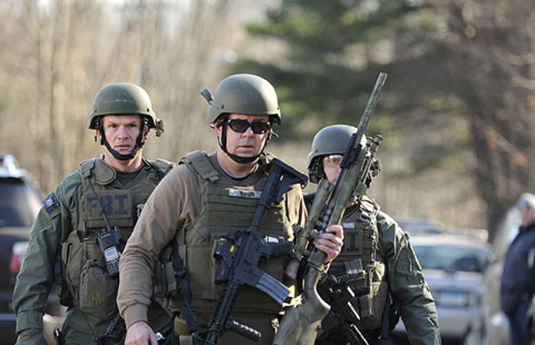 FBI SWAT team members walk along Dickinson Drive near Sandy Hook Elementary School in Newtown, Connecticut, Friday, December 14, 2012. Twenty-seven people, including 18 children, have been killed in a shooting at Sandy Hook Elementary School.