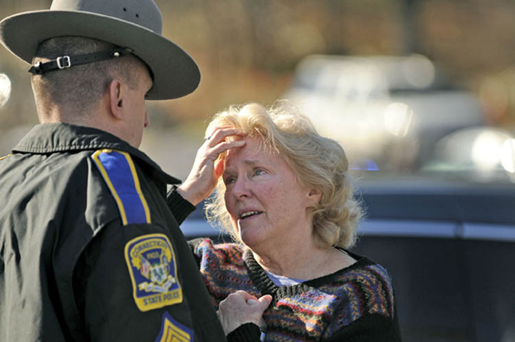 A woman talks to a state police officer at the scene of a shooting at Sandy Hook Elementary School in Newtown, Connecticut, Friday, December 14, 2012. Twenty-seven people, including 18 children, have been killed in a shooting at Sandy Hook Elementary School.