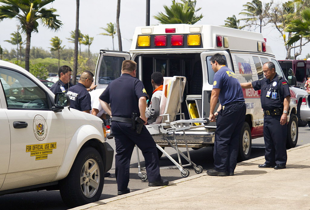A 16-year-old boy, seen sitting on a stretcher center, who stowed away in the wheel well of a flight from San Jose, Calif., to Maui is loaded into an ambulance at Kahului Airport.