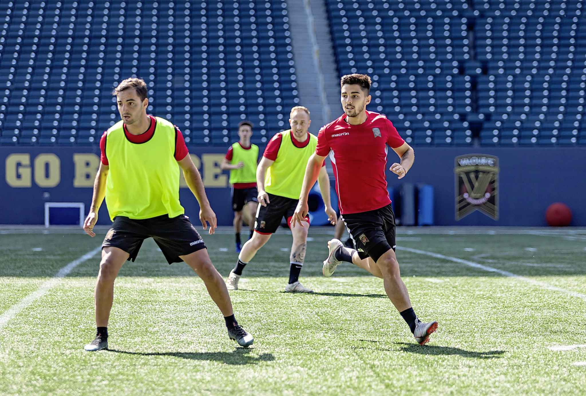 Valour FC Midfielder Dylan Sacramento, right, runs through drills during a team practice on Investors Group Field, Thursday.