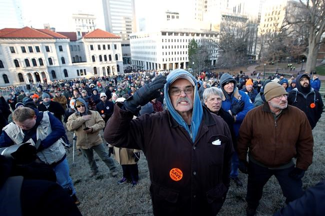 Demonstrators stand on the capitol grounds ahead of a pro gun rally, Monday, Jan. 20, 2020, in Richmond, Va. (AP Photo/Steve Helber)