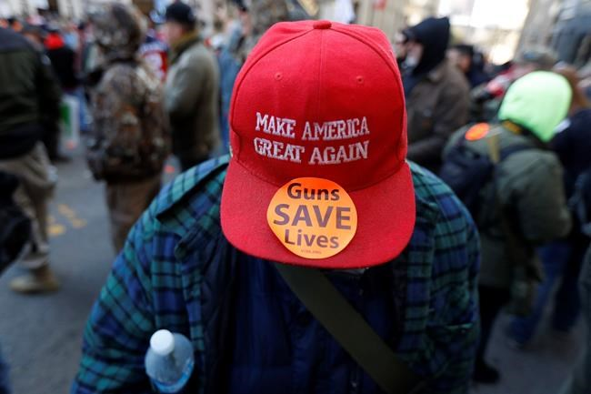 A man walks in the crowd during a pro-gun rally, Monday, Jan. 20, 2020, in Richmond, Va. Thousands of pro-gun supporters are expected at the rally to oppose gun control legislation like universal background checks that are being pushed by the newly elected Democratic legislature. (AP Photo/Julio Cortez)
