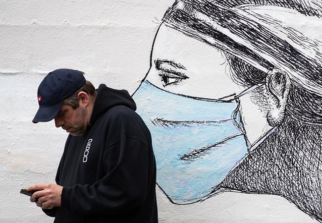 A man looks at his phone while standing near artwork of a woman wearing a protective face mask, on the side of a building in Vancouver, on Sunday, May 31, 2020. THE CANADIAN PRESS/Darryl Dyck