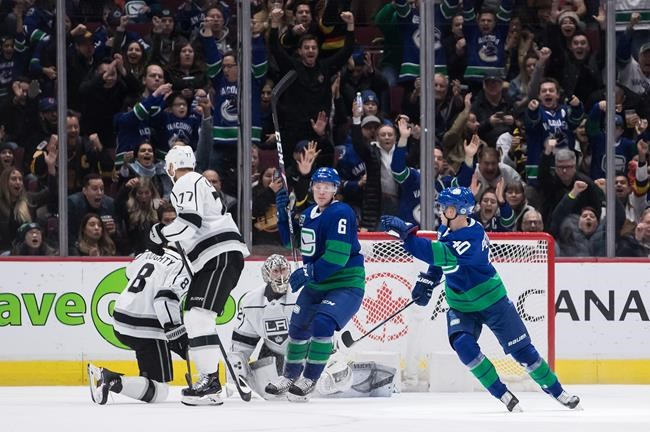 Vancouver Canucks' Elias Pettersson (40), of Sweden, celebrates his goal with teammate Brock Boeser (6) as Los Angeles Kings' Drew Doughty (8) and his teammate Jeff Carter (77) look on during third period NHL hockey action in Vancouver, Saturday, Dec. 28, 2019. THE CANADIAN PRESS/Darryl Dyck