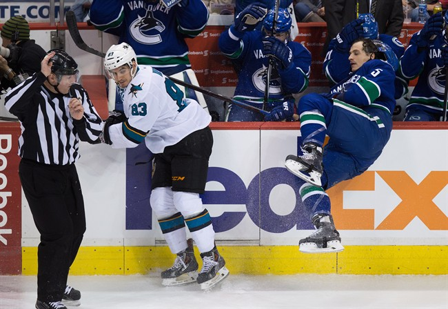San Jose Sharks' Matt Nieto (83) checks Vancouver Canucks' Luca Sbisa, of Switzerland, during the third period of an NHL hockey game in Vancouver, B.C., on Tuesday March 3, 2015. THE CANADIAN PRESS/Darryl Dyck