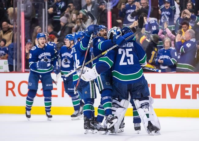 Vancouver Canucks goalie Jacob Markstrom (25), of Sweden, Chris Tanev (8) and Tyler Motte (64) celebrate their win following shootout NHL hockey action against the Calgary Flames, in Vancouver on Saturday, Feb. 9, 2019. THE CANADIAN PRESS/Darryl Dyck