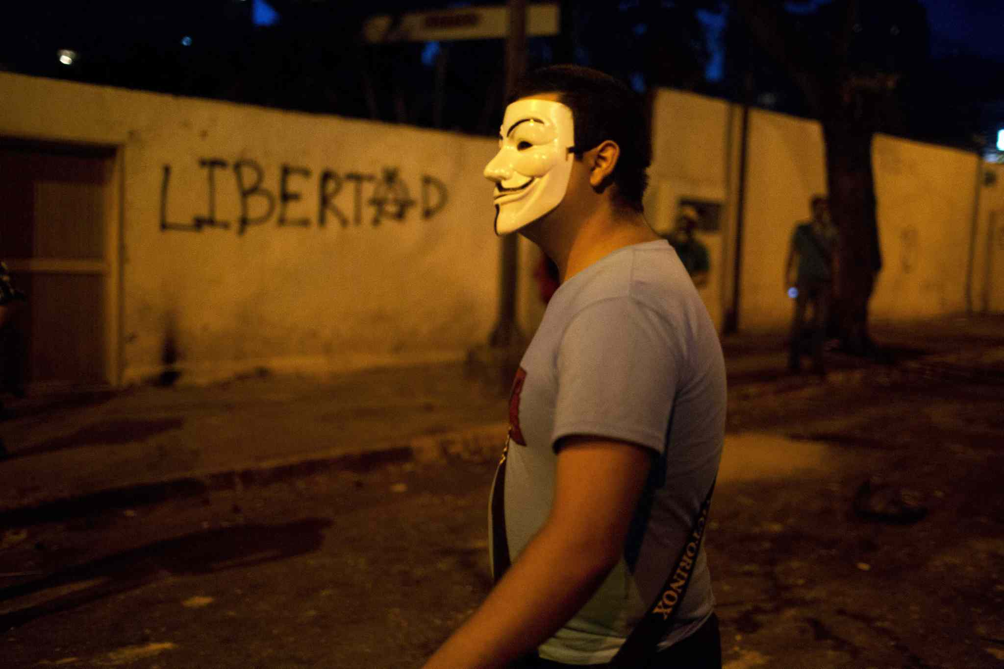 A masked man walks next to graffiti on a wall that reads in Spanish,