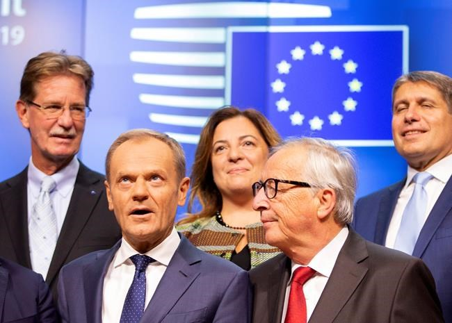 European Commission President Jean-Claude Juncker, second right, and European Council President Donald Tusk, second left, pose during a group photo during a tripartite summit in Brussels, Wednesday, Oct. 16, 2019. European Union and British negotiators have failed to get a breakthrough in the Brexit talks during a frantic all-night session and will continue seeking a compromise on the eve of Thursday's crucial EU summit. (AP Photo/Virginia Mayo)
