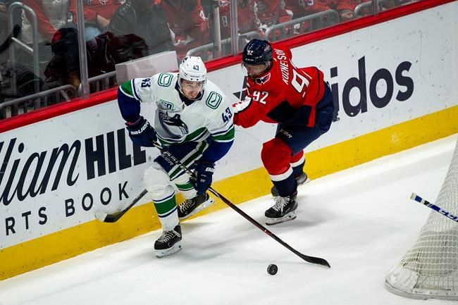 Vancouver Canucks defenseman Quinn Hughes (43) moves the puck past Washington Capitals center Evgeny Kuznetsov (92), from Russia, during the first period of an NHL hockey game, Saturday, Nov. 23, 2019, in Washington. (AP Photo/Al Drago)