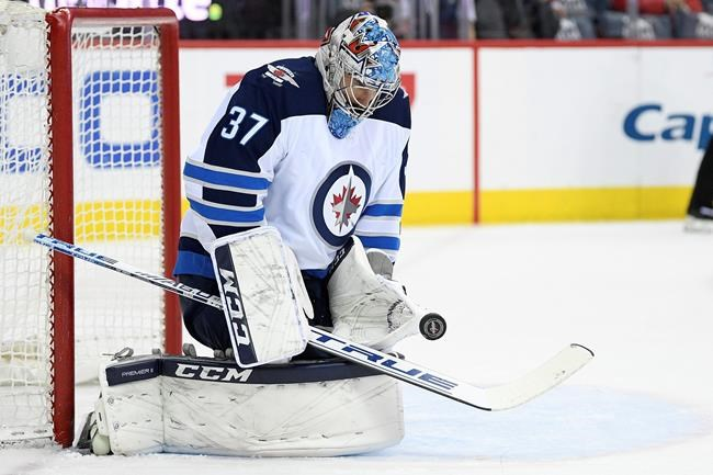 Winnipeg Jets goaltender Connor Hellebuyck (37) stops the puck during the first period of an NHL hockey game against the Washington Capitals, Sunday in Washington.