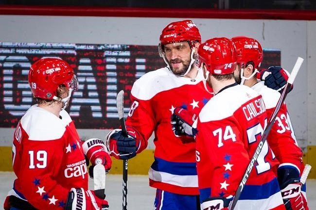 Washington Capitals left wing Alex Ovechkin (8), from Russia, is congratulated by center Nicklas Backstrom (19), from Sweden, defenseman John Carlson (74), and defenseman Radko Gudas (33), from Czech Republic, after scoring during the first period of an NHL hockey game against the New Jersey Devils, Thursday, Jan. 16, 2020, in Washington. (AP Photo/Al Drago)