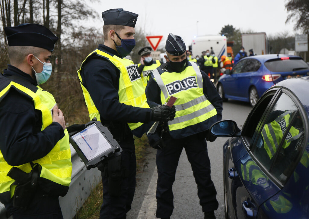 French police officers check cars at the French Belgium border in Neuville en Ferrain, northern France, on Feb. 1 to stop the growing spread of new variants of the virus and avoid a third lockdown. All those arriving from other EU countries will be required to produce a negative virus test. (Michel Spingler / The Associated Press files)