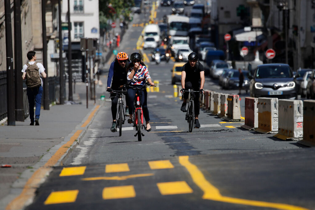 People ride on the new bike lanes in Paris in May, 2020. The French capital enlarged bicycles lanes, shown with yellow painting. (Christophe Ena / THe Associated Press files)